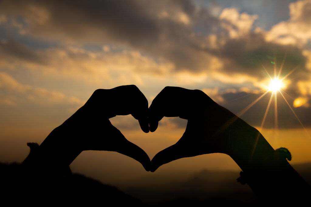 Heart shape from two hand with sunrise background.