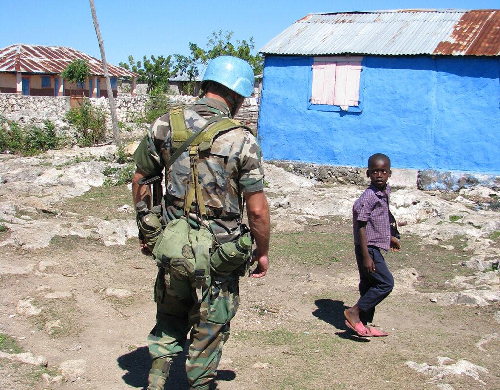 soldier of the 'United Nations Stabilisation Mission in Haiti' on patrol encountering Haitian boy , Haiti, Grande Anse, Jeremie