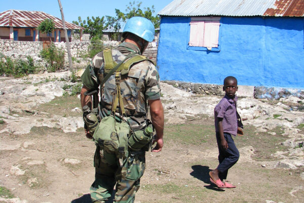 soldier of the 'United Nations Stabilisation Mission in Haiti' on patrol encountering Haitian boy , Haiti, Grande Anse, Jeremie